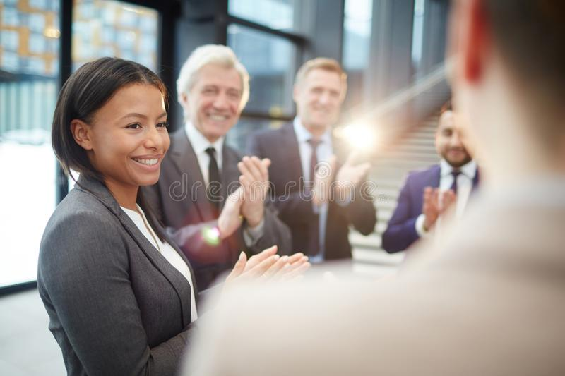 Greeting winner. Happy female politician and her colleagues greeting speaker with ovations and congratulating him on victory stock photo
