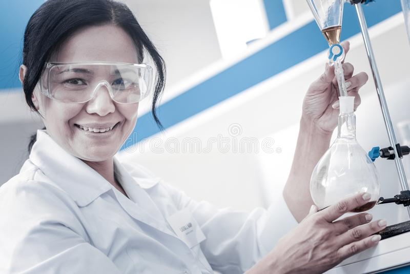 Happy female researcher smiling while pouring liquid into flask stock photo