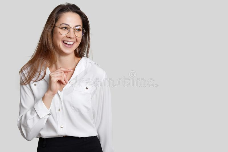 Happy female secretary dressed in black and white clothes, wears transparent round glasses, has toothy smile, laughs at good joke stock image