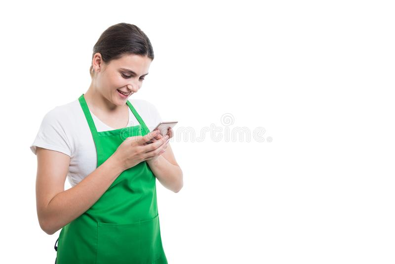 Happy female seller texting on cellphone royalty free stock images