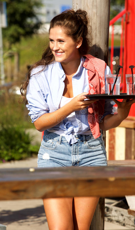 Happy female server holding tray with drinks outside stock image