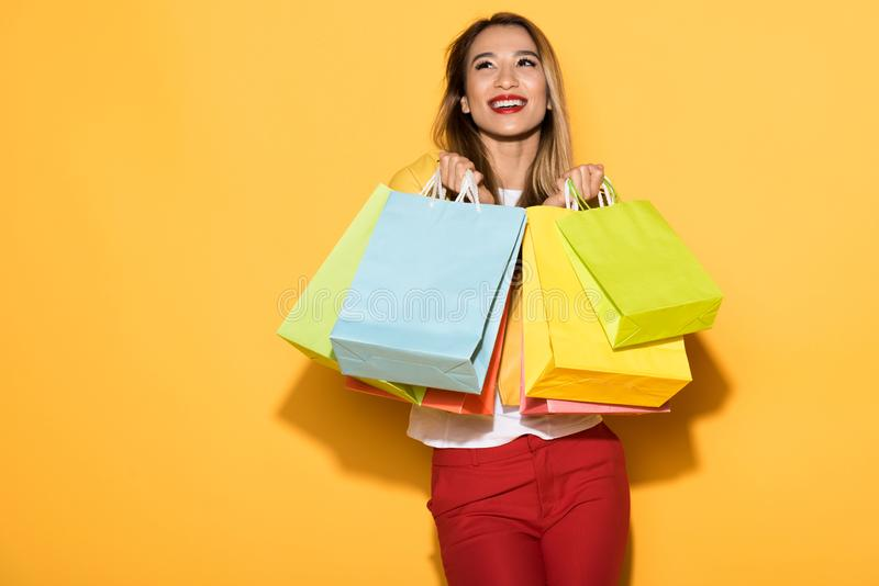 happy female shopper standing with paper bags on yellow stock photos