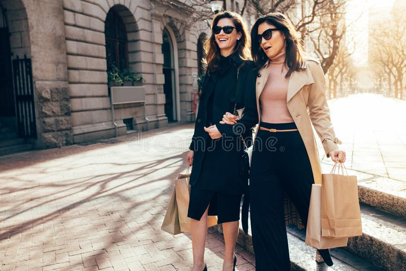 Happy female shoppers carrying shopping bags royalty free stock photo