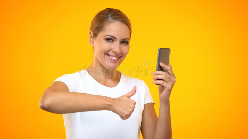 Happy female showing thumbs up holding smartphone, shopping online, internet. Stock photo stock photography