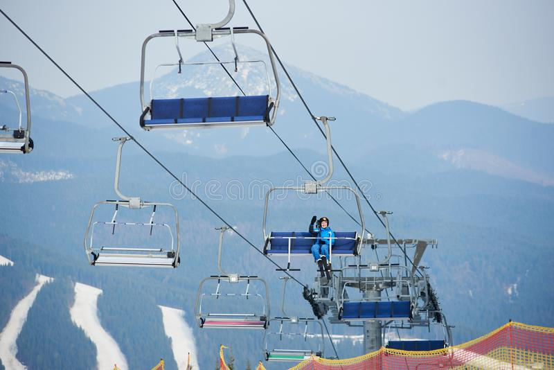 Happy female skier in blue ski suit sitting on a cable ski lift with skies at winter ski resort, waving hand. Ski slopes and mountains on the background stock image