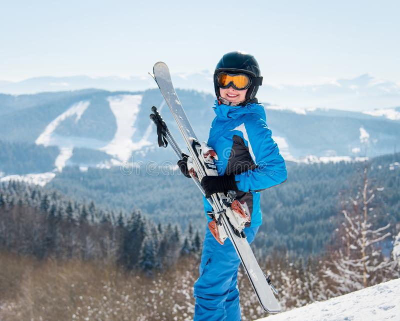 Happy female skier smiling to the camera, holding her skis, wearing blue ski suit and black helmet at winter ski resort. Happiness positivity vacation stock images