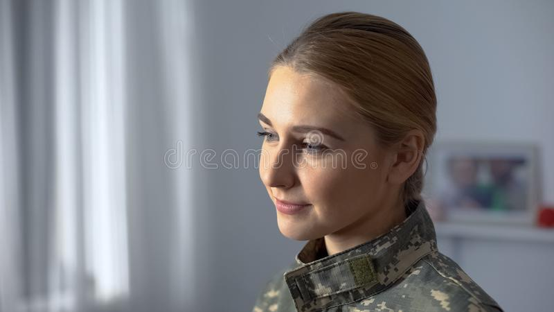 Happy female soldier in camouflage uniform watching military march in window royalty free stock photos
