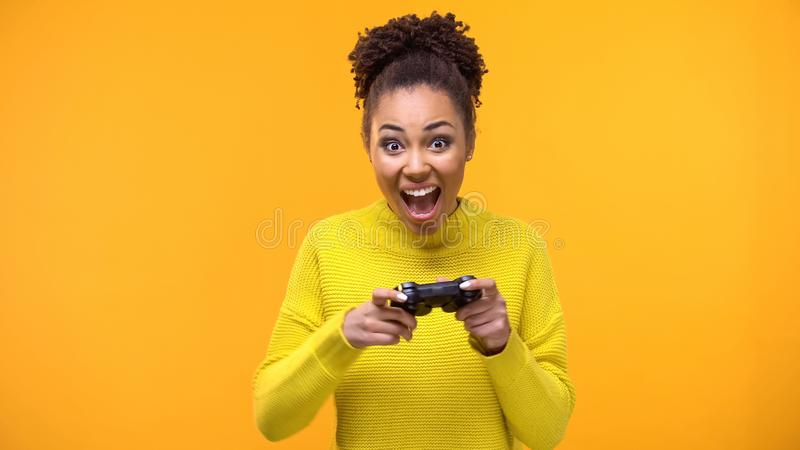 Happy female student with game joystick yellow background, hobby excitement royalty free stock photography