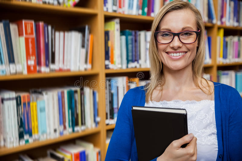 Happy female student holding a book in the library royalty free stock image
