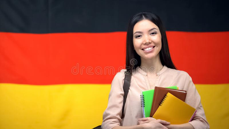 Happy female student holding copybooks against German flag background, education stock image