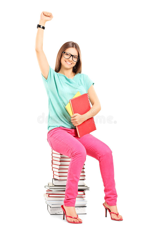 Happy female student sitting on a stack of books royalty free stock images