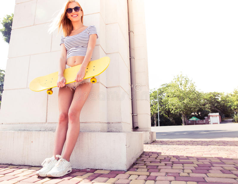 Happy female teenager holding skateboard. Full length portrait of a happy female teenager holding skateboard and leaning on the wall outdoors royalty free stock images