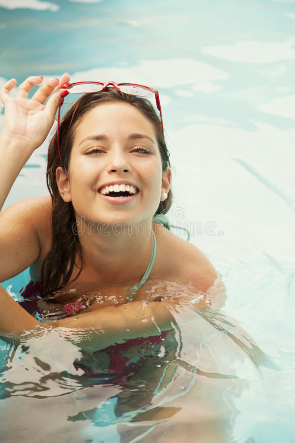 Happy female teenager in swimming pool royalty free stock photo