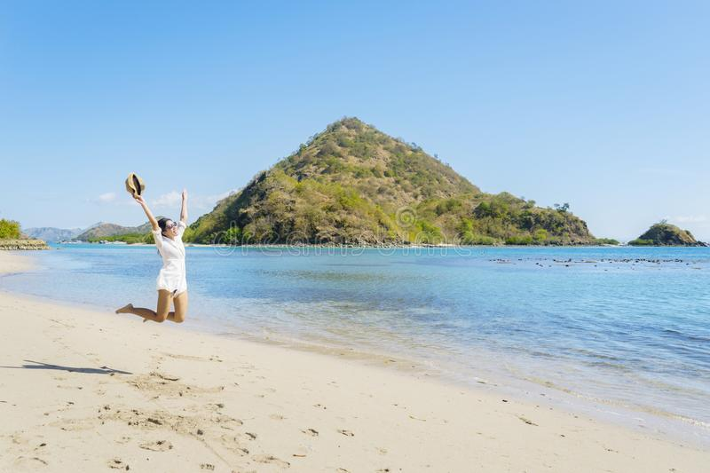 Happy female tourist enjoying her summer vacation. Image of happy female tourist leaping on the tropical beach while enjoying her summer vacation in Labuan Bajo royalty free stock image