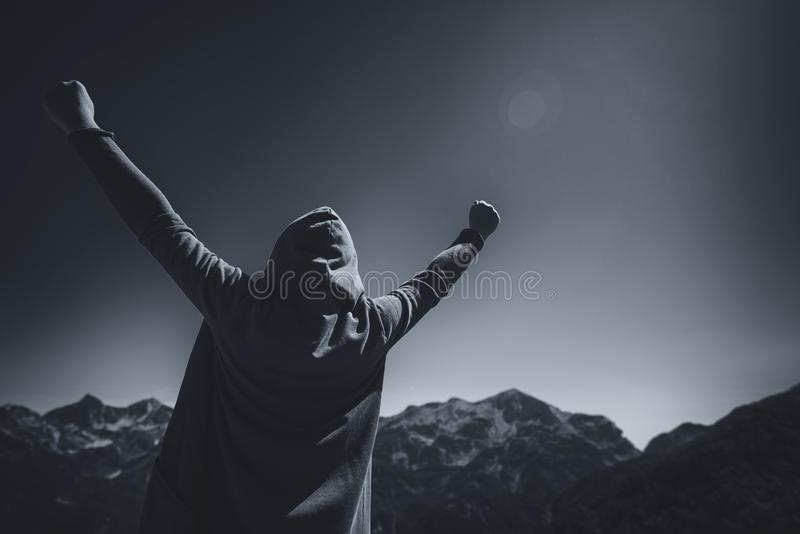 Happy female traveler with hands raised at mountain top royalty free stock photos