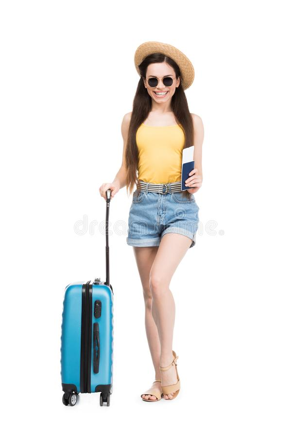 Happy female traveler with passport, air ticket and baggage,. Isolated on white stock images