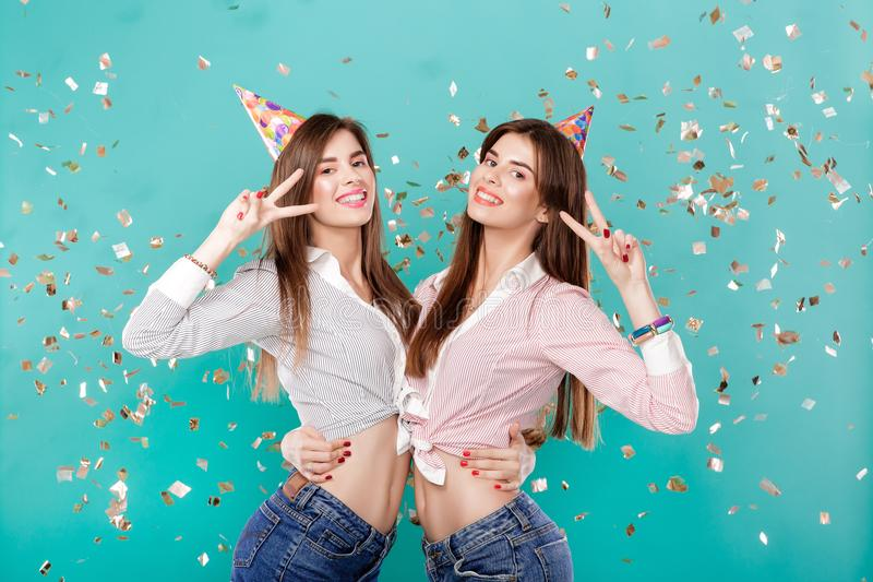 Women in birthday hat and confetti on blue background. Happy female twins in birthday hat and gold confetti on blue background. Celebration and party. Having royalty free stock photography