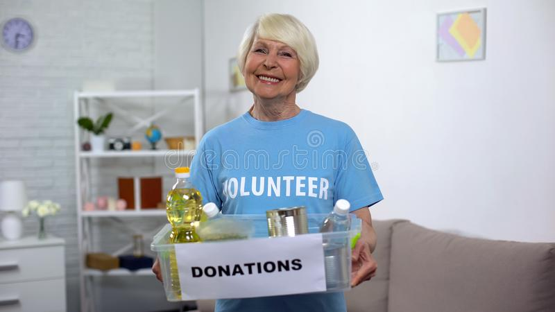 Happy female volunteer holding donation box, food for poor people, assistance royalty free stock image