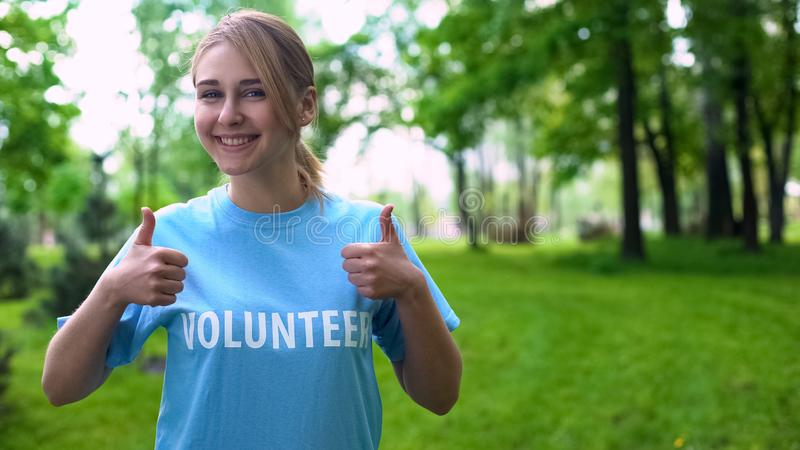 Happy female volunteer showing thumbs up standing in forest, natural resources stock image