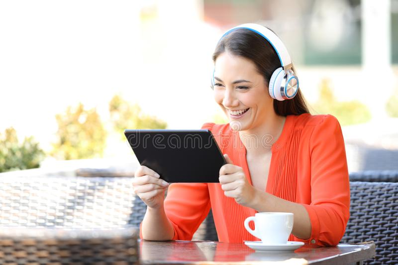 Happy female watching media content on tablet stock photos