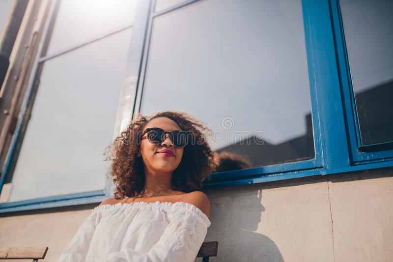 Happy female wearing sunglasses sitting outside. Shot of attractive young african woman sitting outdoors and looking away. Happy female wearing sunglasses stock photos