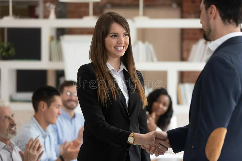 Happy female worker get rewarded for good work handshake boss. Happy excited female worker intern get rewarded for good work result handshake boss, proud ceo royalty free stock photos