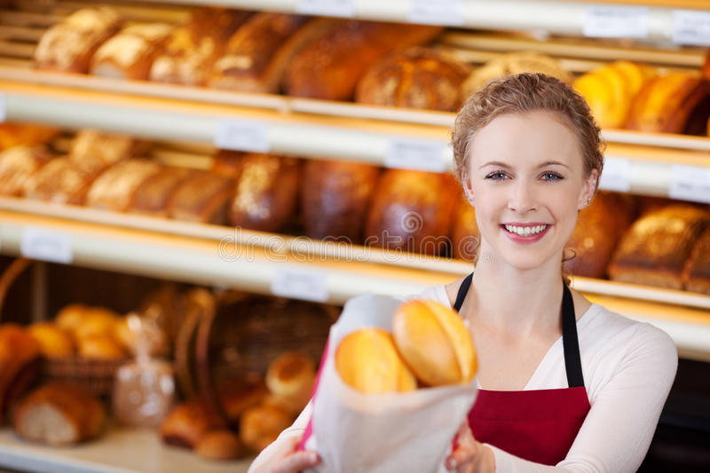 Happy Female Worker Giving Bag Of Breads. Portrait of happy female worker giving bag of breads in bakery royalty free stock photo