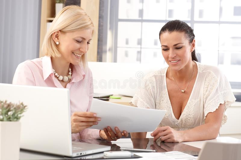 Happy female workers at business office. Happy casual female workers at business office working in front of laptop computer checking report papers, smiling royalty free stock photos