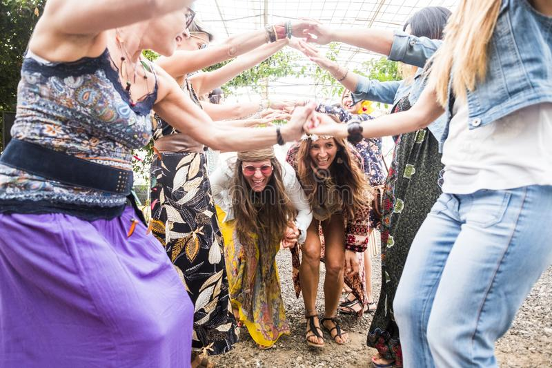 Happy females with colorful and hippy clothes and dress have fun together celebrate an event with plays and dance. old and young stock images