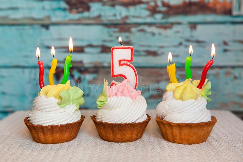 Happy fifth birthday cake and number five candle on blue background, anniversary celebration royalty free stock photos