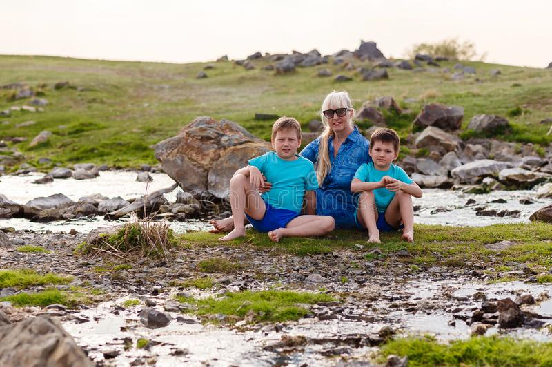 Happy fifty-year-old woman embraces two children stock photography