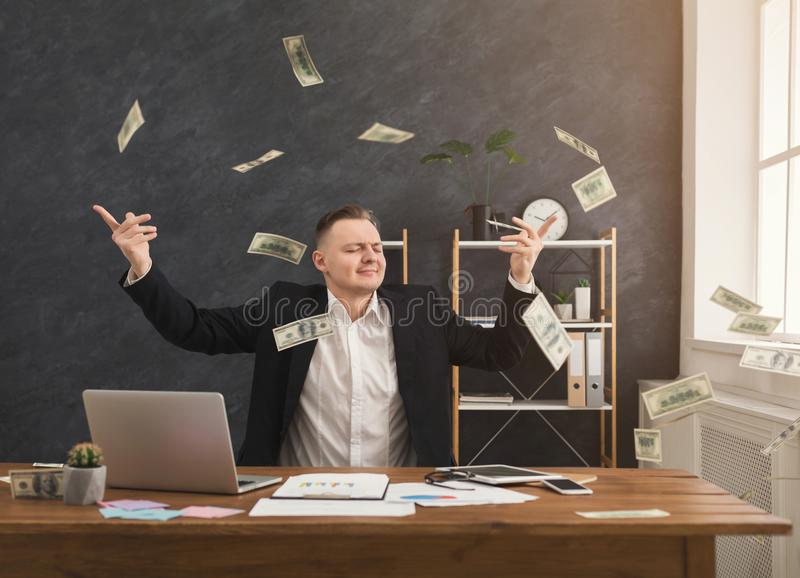 Financier man throwing out dollars in office. Happy financier man sitting in office and holding dollars. Man throwing out money, copy space stock photography