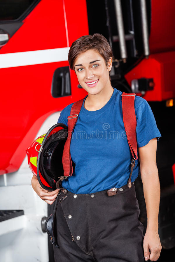 Happy Firefighter Holding Helmet Against Firetruck royalty free stock image