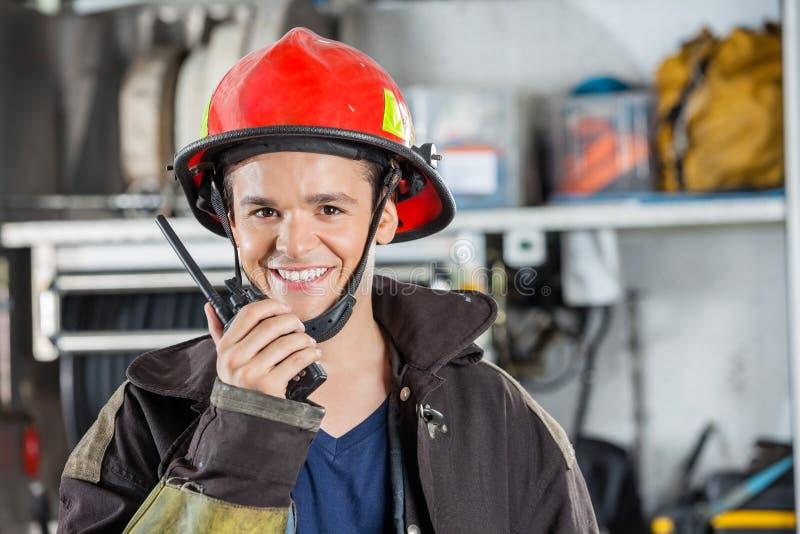 Happy Fireman Using Walkie Talkie. Portrait of happy young fireman using walkie talkie at fire station royalty free stock photo