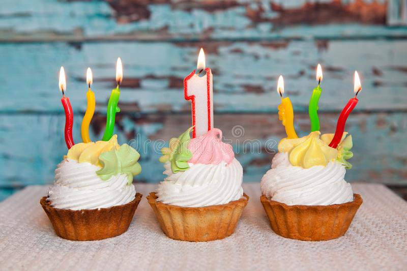 Happy first birthday cake and number one candle on blue background royalty free stock photo