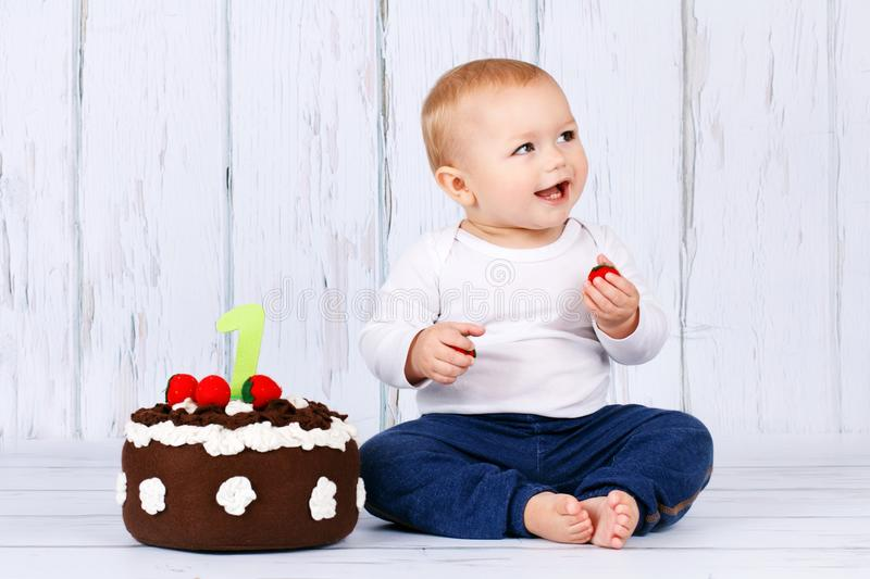 Happy first birthday, studio portrait of cute toddler and a birthday cake. Laughing boy sitting on the floor royalty free stock image