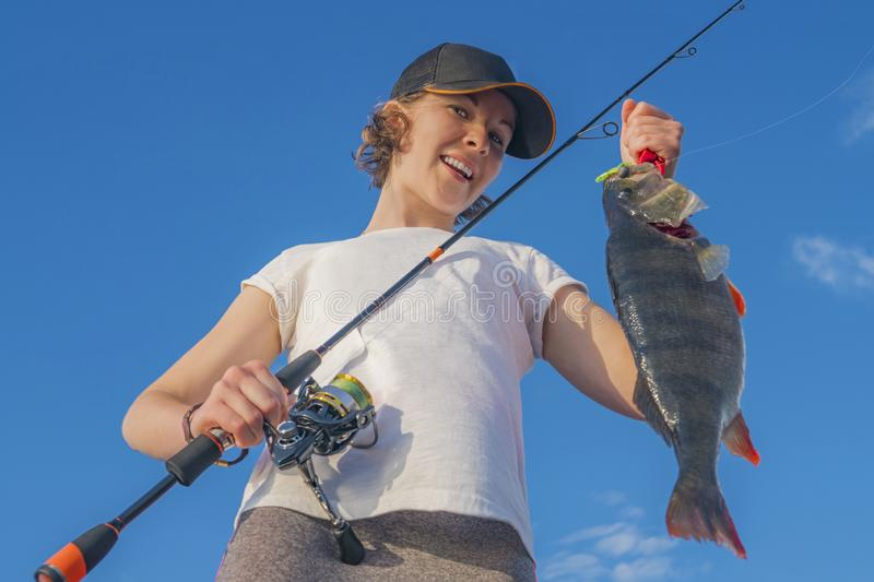 Happy fisher girl with perch fish trophy at the boat royalty free stock photos