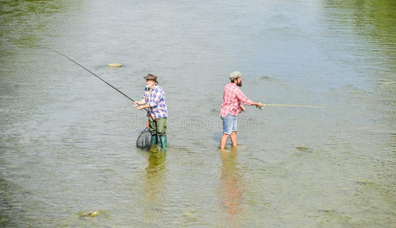 Happy fisherman with fishing rod and net. Hobby and sport activity. Male friendship. Father and son fishing. Fishing. Together. Teach men to fish and you feed royalty free stock images