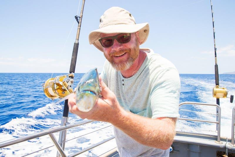 Man holding fresh caught Mahi Mahi on ocean boat. Happy fisherman holding fresh caught Mahi Mahi stock photo