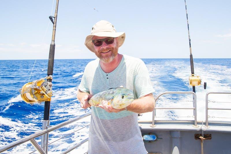 Man holding fresh caught Mahi Mahi on ocean boat. Happy fisherman holding fresh caught Mahi Mahi royalty free stock photography