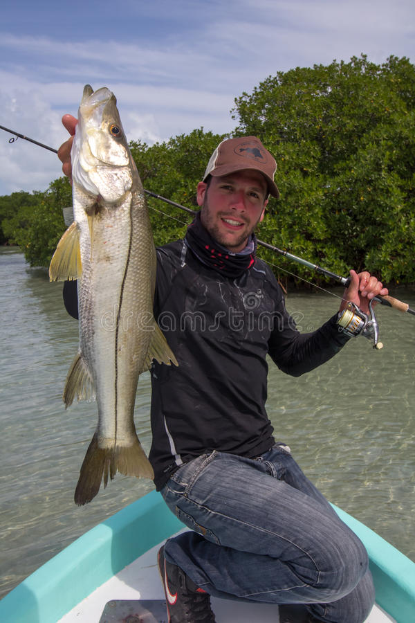 Happy Fisherman holding a good size Snook. A man holding a Snook fish caught with lure, somewhere on the flats of Belize next too a mangrove. This fish is known stock photos