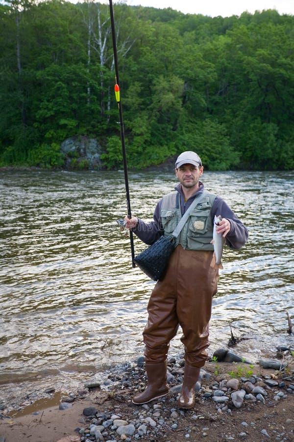 Happy fisherman holds captive salmon. royalty free stock photo