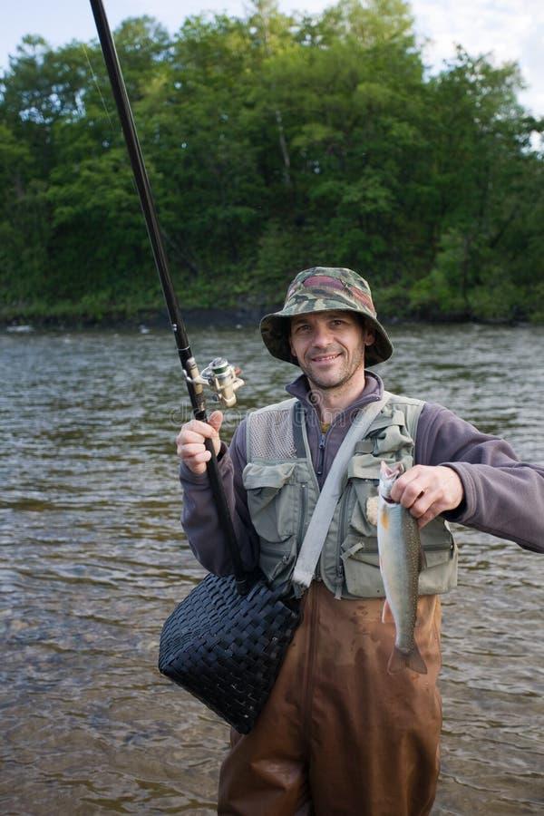Happy fisherman holds salmon. stock photography