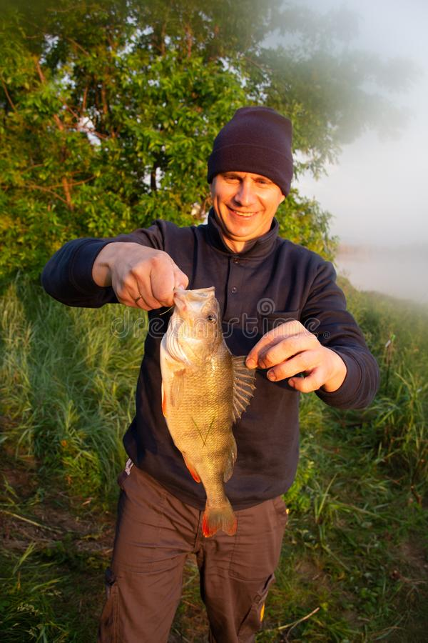 Happy fisherman presents perch, caught big fish. stock photography