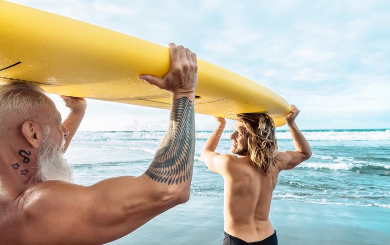 Happy fit friends having fun surfing on tropical ocean - Surfers father and son doing stretching surf exercises royalty free stock image
