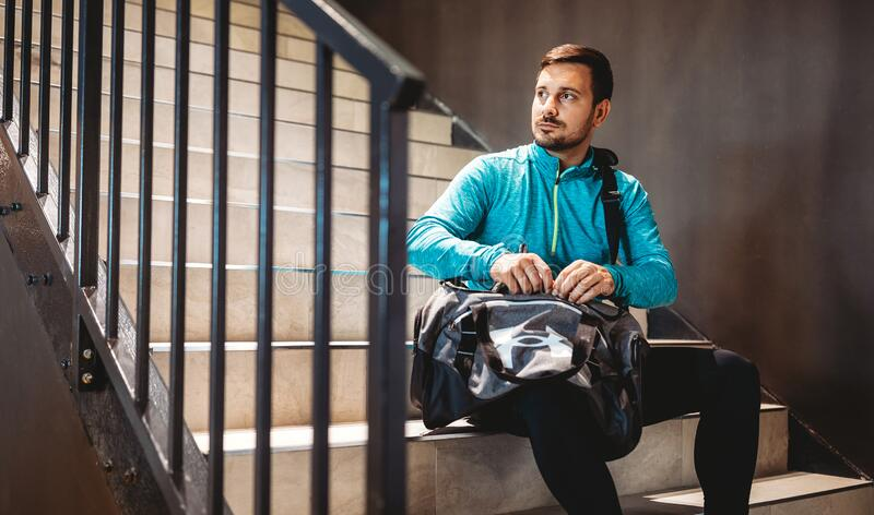 Happy fit man relaxing in the gym after strength exercises for different muscles royalty free stock images