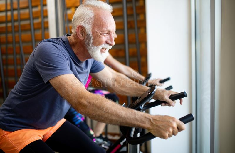Happy fit mature woman and man cycling on exercise bikes to stay healthy royalty free stock images