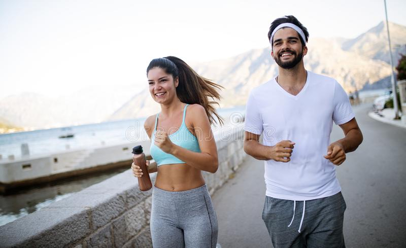 Healthy sporty lifestyle. Happy fit people friends exercising and running outdoor royalty free stock image