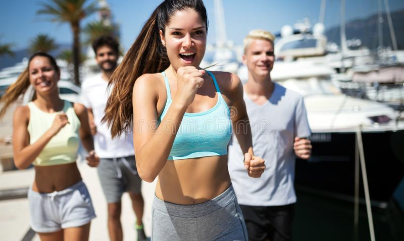 Happy fit people running and jogging together in summer sunny nature royalty free stock photo