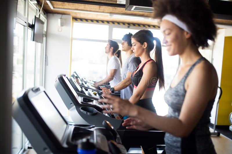 Happy fit people running on treadmill at fitness gym club. Healthy fit people running on treadmill at fitness gym club stock photo